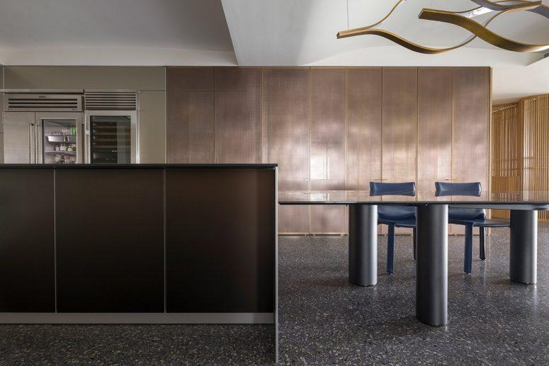 La cuisine est faite avec des armoires sombres et métalliques élégantes, il y a une grande table et quelques chaises bleues