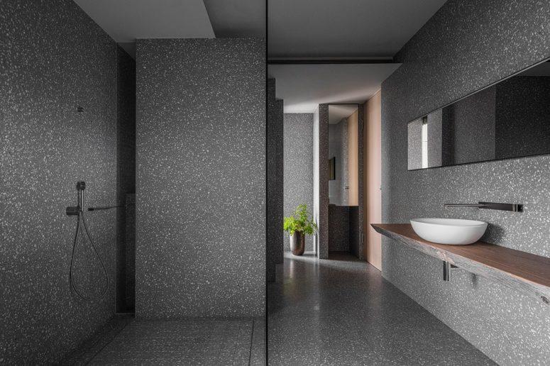 La salle de bain est revêtue de terrazzo gris et dispose d'un peu de bois pour l'adoucir