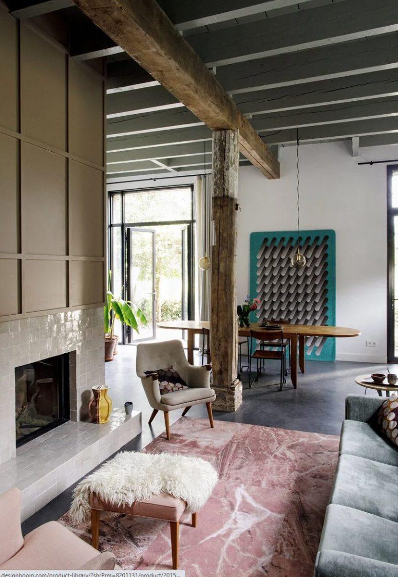 Le salon est fait avec une cheminée revêtue de carreaux blancs, un canapé gris, poutres et piliers en bois, un espace repas avec une table ovale est attenant ici