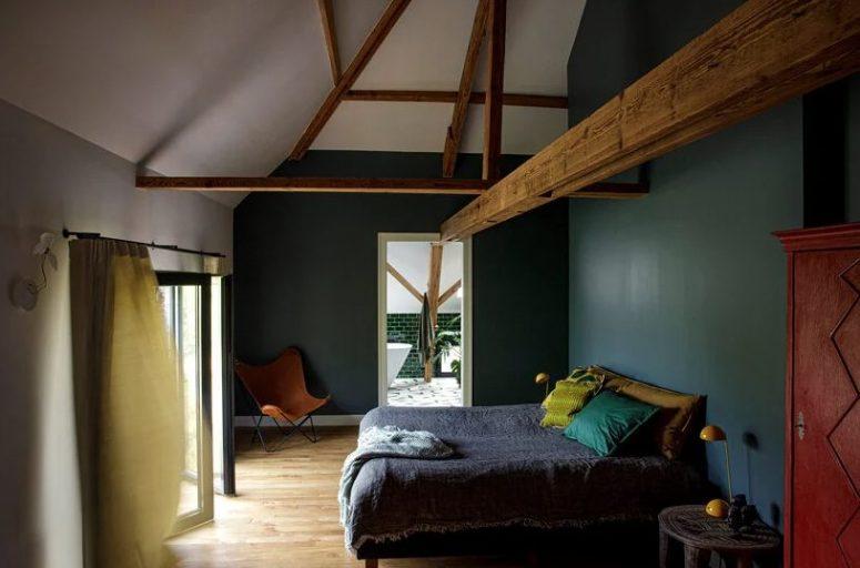 La chambre est de mauvaise humeur, avec des murs verts de chasseur, des textiles lumineux, des poutres en bois qui ajoutent du charme et une sensation vintage