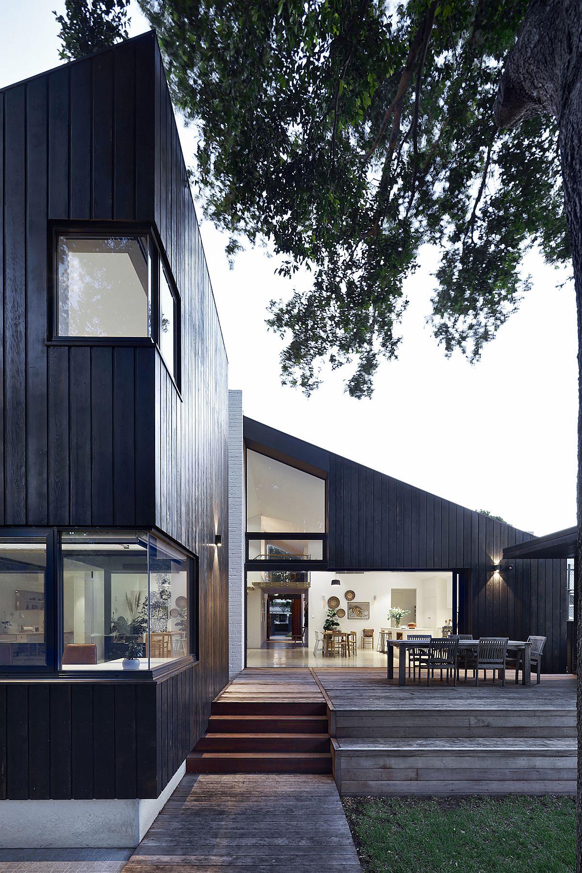 La grande terrasse en bois prolonge le salon à l'extérieur et relie l'intérieur avec le jardin