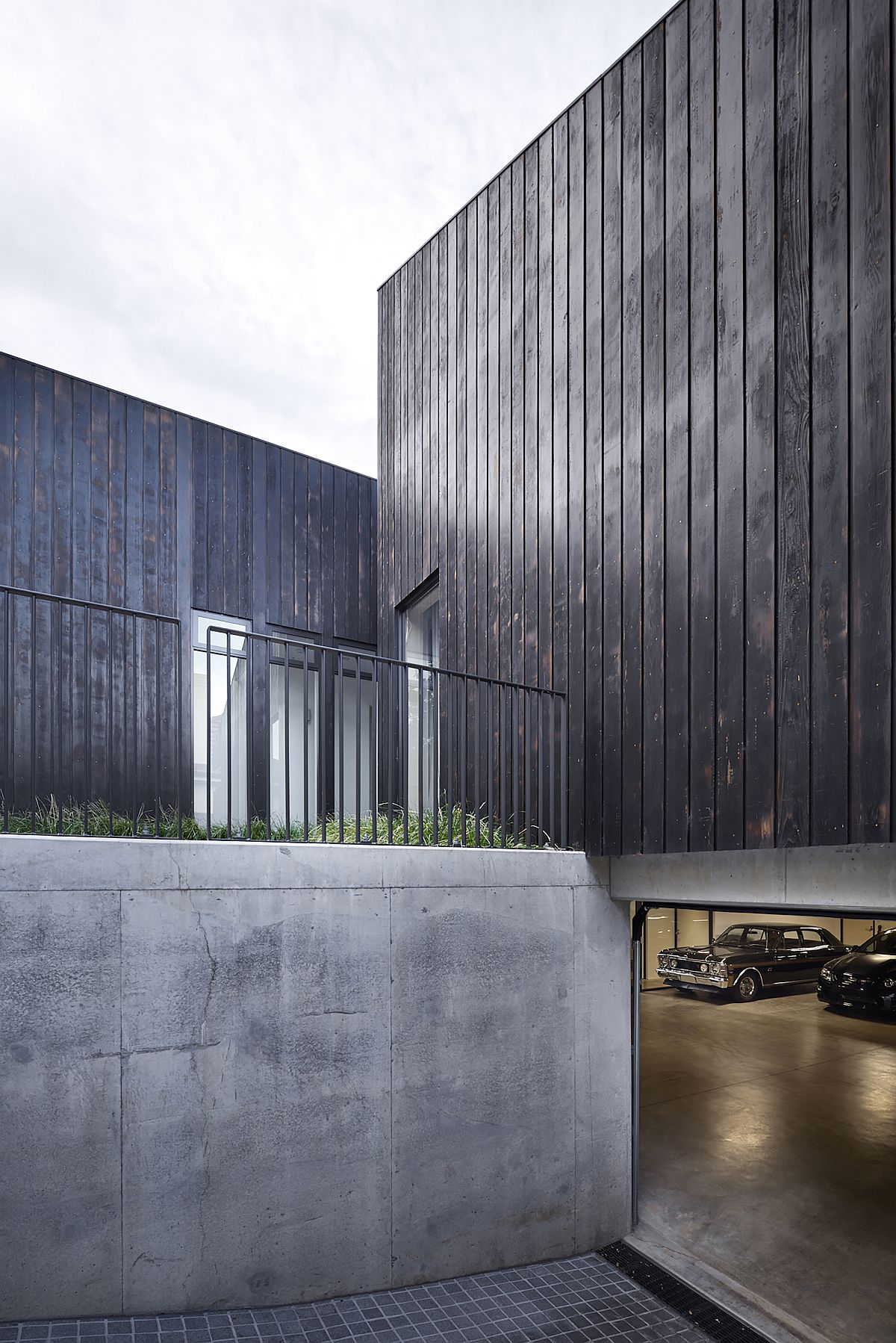 Le garage caché sous le niveau du sol de la maison est élégant et minimal