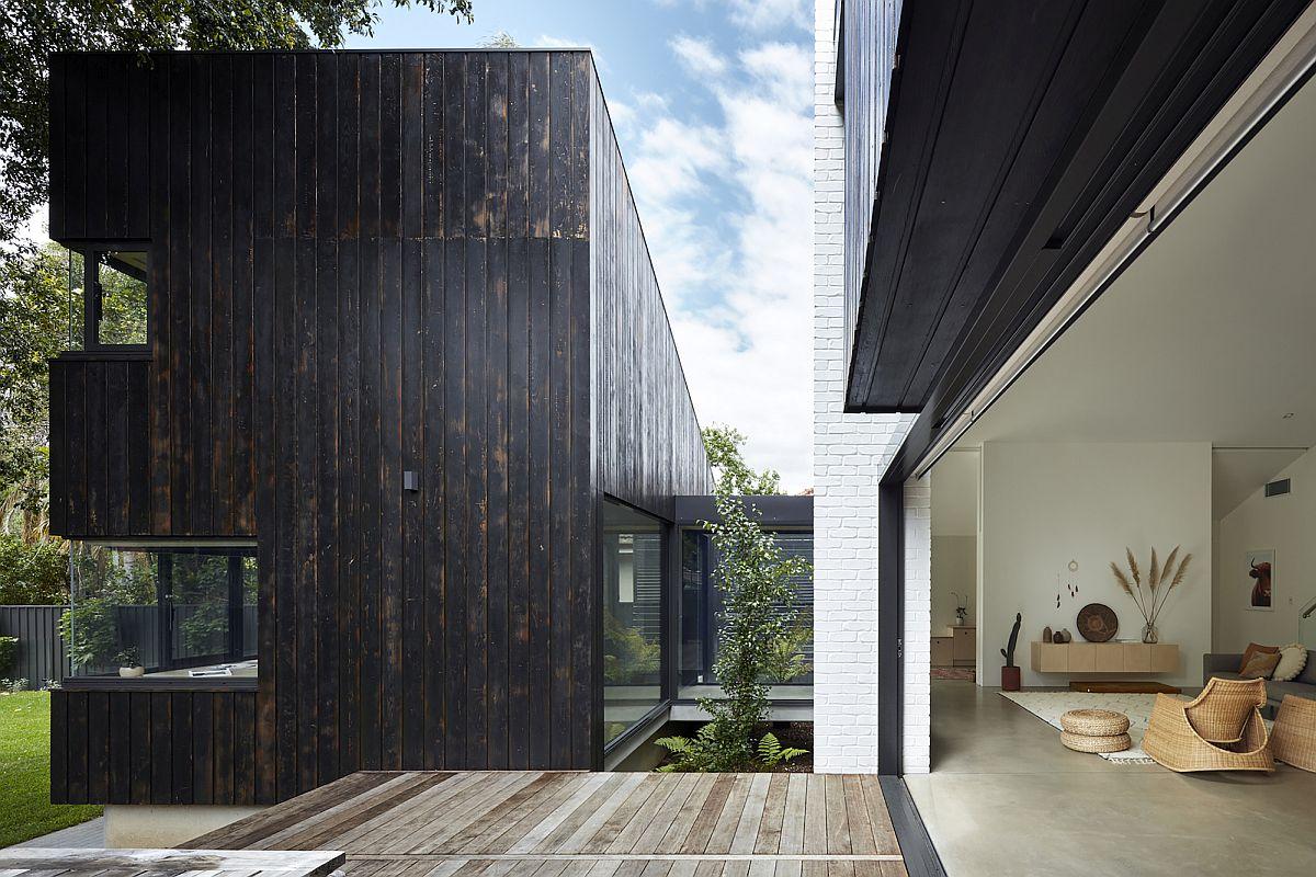 La transition entre les finitions en bois sombres et carbonisées et les éléments intérieurs plus clairs est transparente