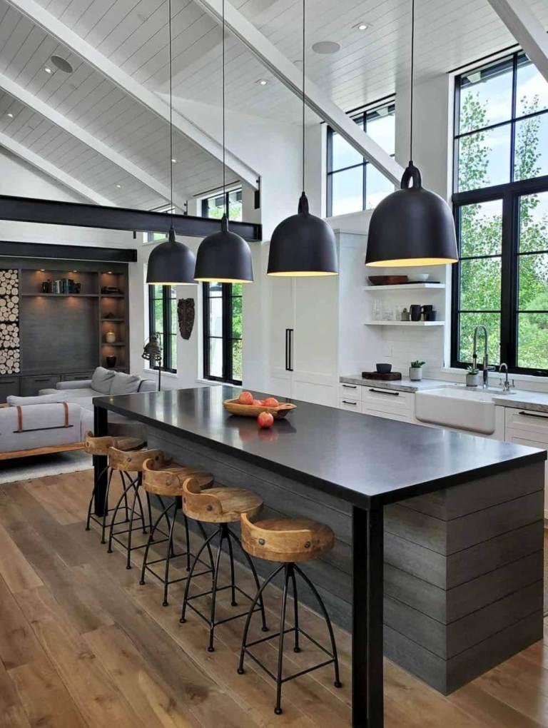 La cuisine est faite avec des armoires blanches, avec un îlot de cuisine sombre, des suspensions et des tabourets en bois