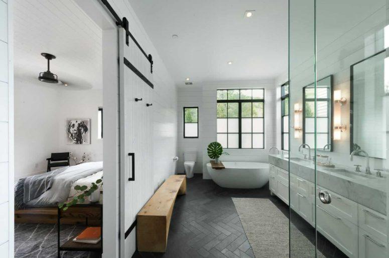 La suite principale a une grande et élégante salle de bain avec de grandes fenêtres et une porte de grange coulissante