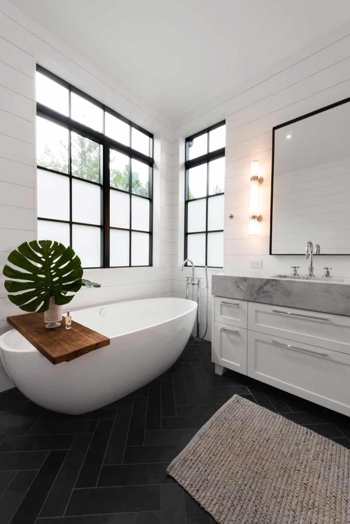 Une baignoire ovale est placée à l'extrémité de la salle de bain, où elle est encadrée par les deux fenêtres