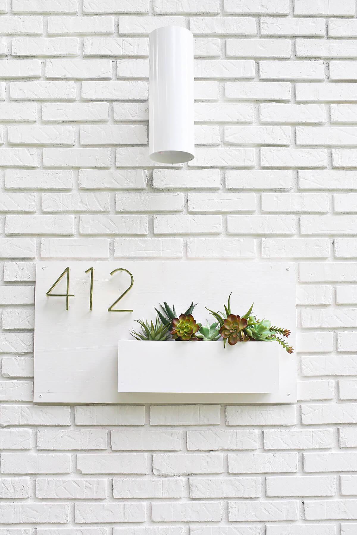 Plaque de numéro de maison sobre avec jardinière