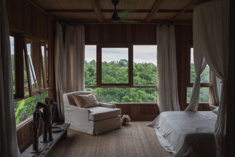 Cette chambre est entièrement vitrée, il y a un lit à baldaquin, des œuvres d'art audacieuses et une chaise