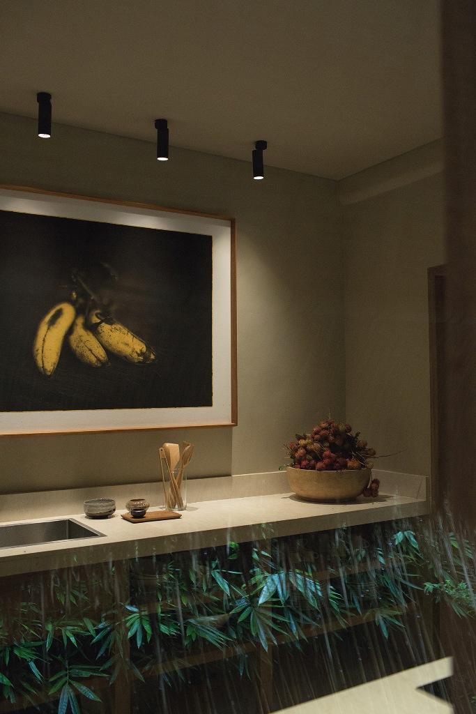 La salle de bain présente du béton et de la pierre neutres ainsi que des touches de bois
