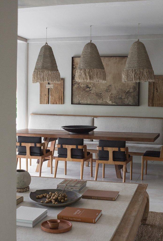 L'espace salle à manger est fait avec des chaises comofrtables, des suspensions tissées et des pièces de la maison accrochées comme un mur de galerie