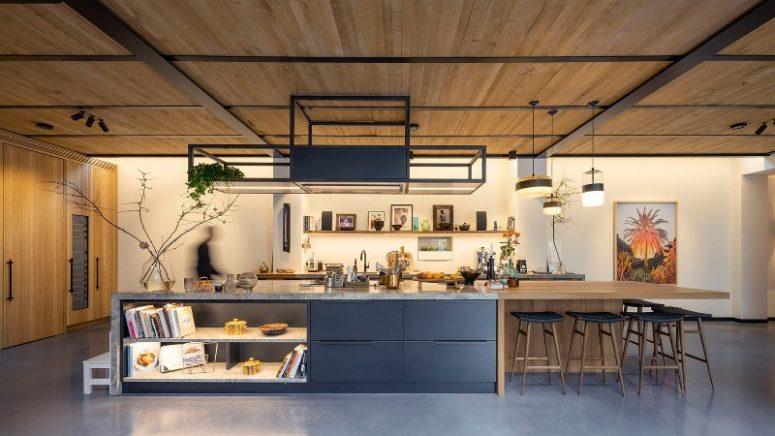 La cuisine est faite avec des armoires en métal sombre, il y a un petit bar en bois, avec de nombreuses lumières et des tabourets en bois