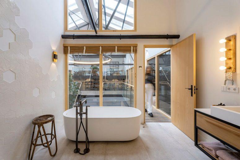 La salle de bain est simple et minimaliste, avec de grandes fenêtres, une baignoire ovale et une grande vanité