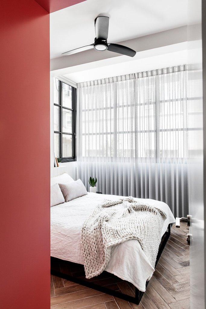 La chambre est inondée de lumière et ne comporte que les meubles les plus nécessaires et un accent rouge