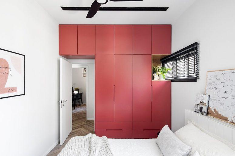 Cet accent rouge est une unité de rangement élégante qui prend tout un mur