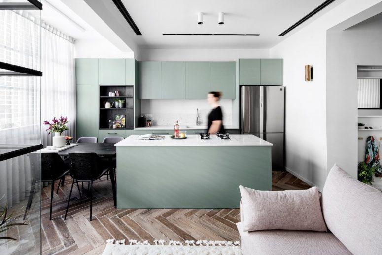 La cuisine et la salle à manger sont également ici, les armoires sont vertes, avec des comptoirs en mable et un dosseret, une table et des chaises noires