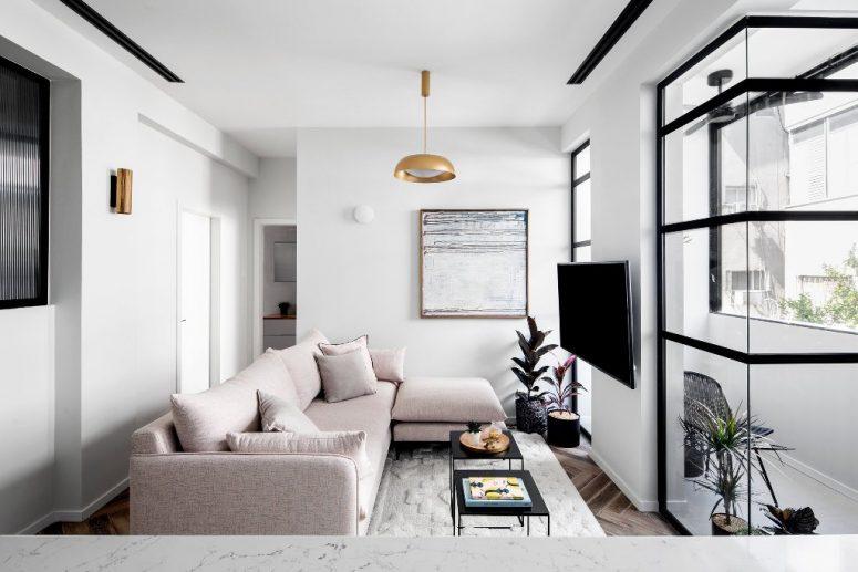 Le salon comprend une section blush, une œuvre d'art, des touches de laiton et une entrée sur le balcon
