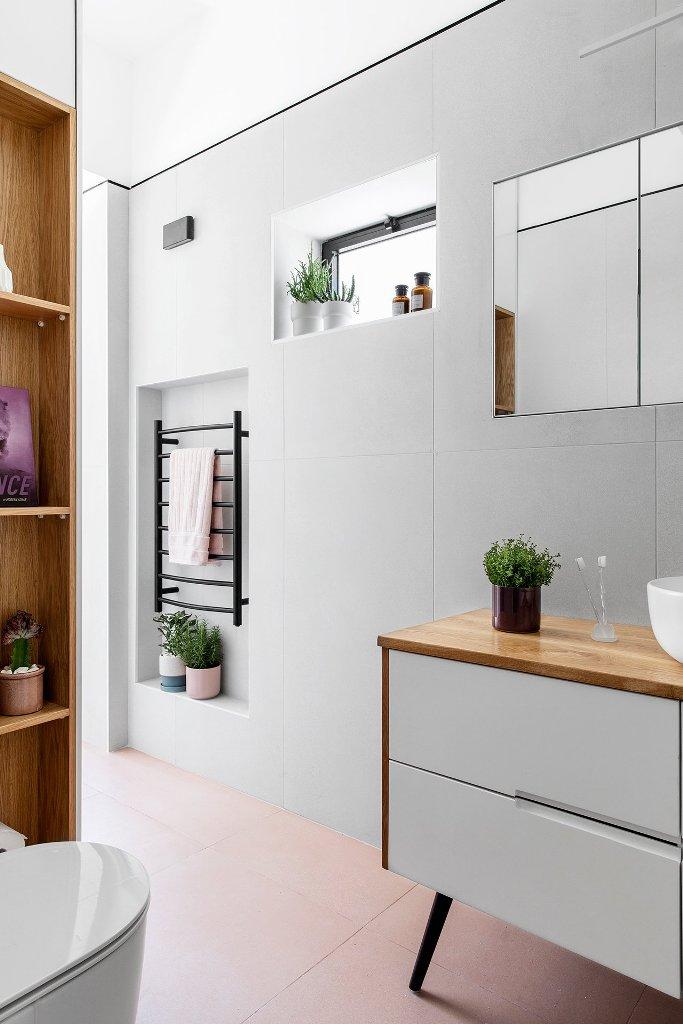 La salle de bain est élégante et neutre, avec de petites fenêtres, des niches pour le rangement