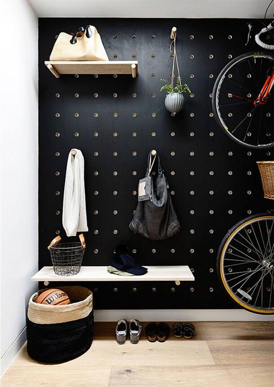 un mur en panneau perforé noir est idéal pour une entrée, ajoutez des étagères et des crochets partout où vous le souhaitez et rendez l'espace plus fonctionnel