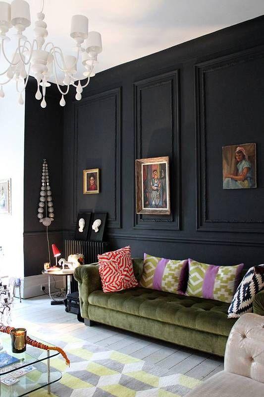 un panneau mural noir fait une déclaration dans cet espace, avec des couleurs neutres et douces, un canapé vert et des œuvres d'art raffinées