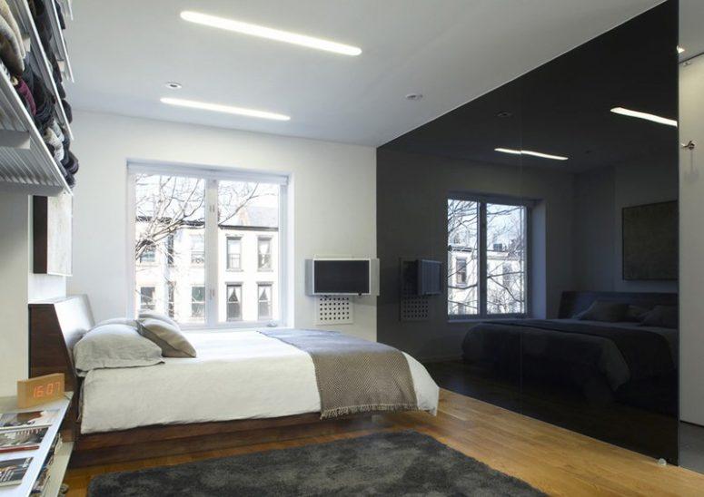 une chambre monochromatique minimaliste avec un mur noir brillant qui apporte du drame et peut cacher une salle de bain