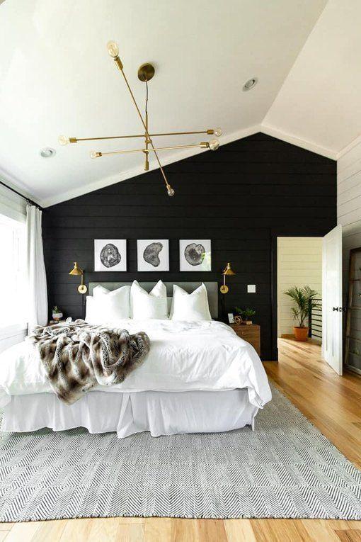 une chambre de ferme moderne avec un mur de planches de bois noir qui fait une déclaration et des touches d'or et de laiton pour un look brillant