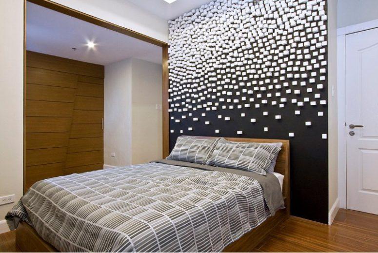 une chambre contemporaine avec un mur noir et un motif géométrique 3D dessus pour un effet galatique est wow