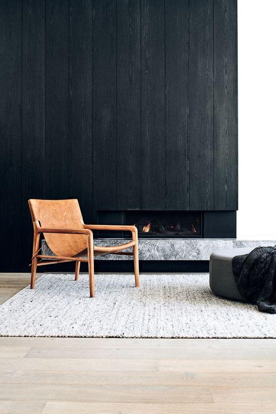 un mur en bois spectaculaire avec une cheminée intégrée et un manteau de dalle de marbre en dessous est une solution chic pour un espace minimaliste