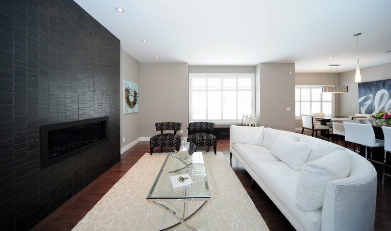un salon contemporain avec un mur de cheminée en carrelage noir, un grand canapé incurvé en blanc et des meubles élégants autour