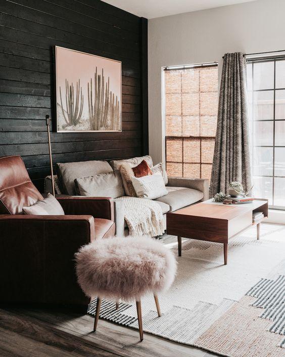 un salon aux couleurs neutres et chaudes avec un mur de planches noires, des meubles neutres, des textiles et des tissus d'ameublement roses et terre cuite