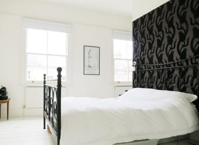 une chambre monochromatique d'inspiration vintage avec un mur de papier peint à fleurs noir, un lit forgé noir et une œuvre d'art chic