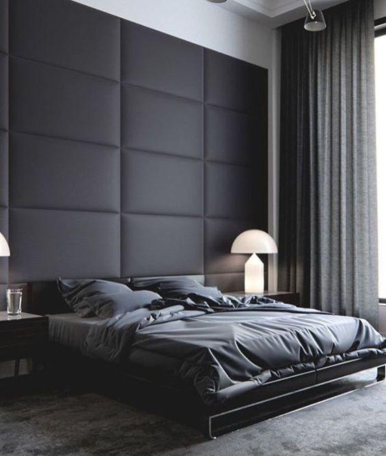 un espace masculin maussade avec un mur noir rembourré qui apporte douceur et confort à la décoration de la pièce