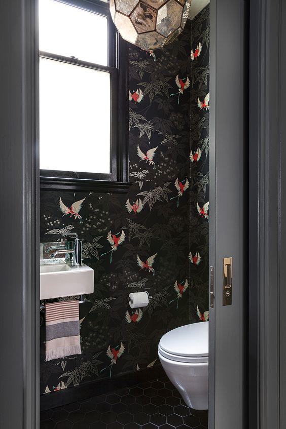 des toilettes de mauvaise humeur et raffinées avec du papier peint à imprimé faune noire, des carreaux blakc au sol et une lampe à facettes dorée raffinée