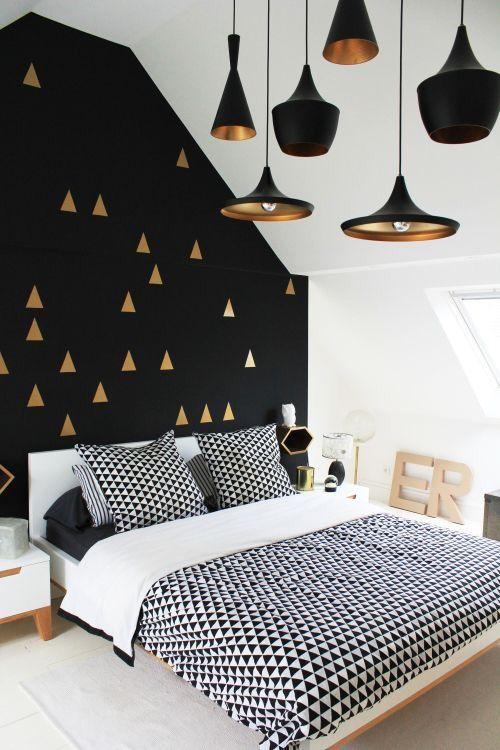 un espace Scandi avec une sensation moderne du milieu du siècle et un mur noir avec un imprimé triangle doré
