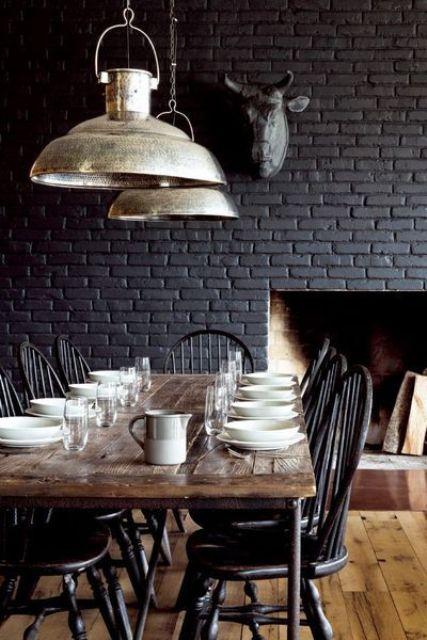 un vintage rencontre une salle à manger rustique avec un mur de briques noires, une table en bois et des chaises vintage sombres est très confortable