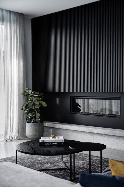 un mur de lattes de bois noir élégant avec une cheminée intégrée est une déclaration audacieuse qui apportera une touche dramatique à l'espace