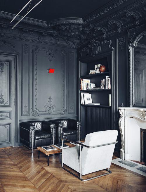 un salon raffiné avec de magnifiques murs noirs et un plafond avec moulures et lambris, des meubles en noir et blanc pour un look contrasté