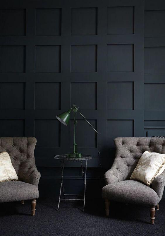 un mur lambrissé noir raffiné et un mobilier vintage créent une ambiance chic et exquise dans ce salon