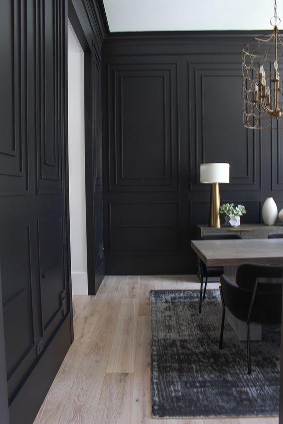 une salle à manger élégante avec des murs lambrissés noirs, une table en bois, une crédence et des lampes dorées