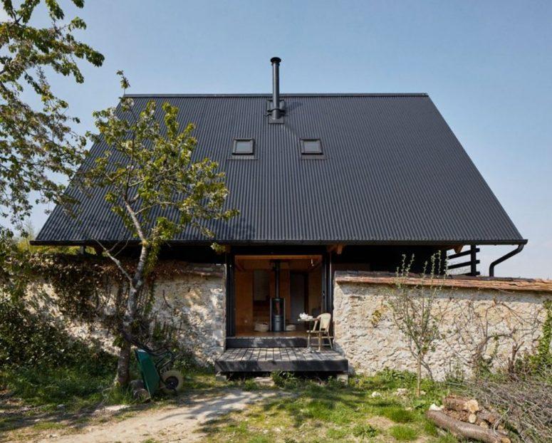 L'arrière de la maison ressemble à ceci - les espaces intérieurs peuvent être ouverts sur l'extérieur, il y a un mur de pierre entourant la maison