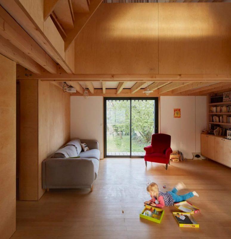 Le salon montre aussi beaucoup de livres, il y a un canapé moderne et une chaise vintage, c'est un grand espace de jeu pour l'enfant