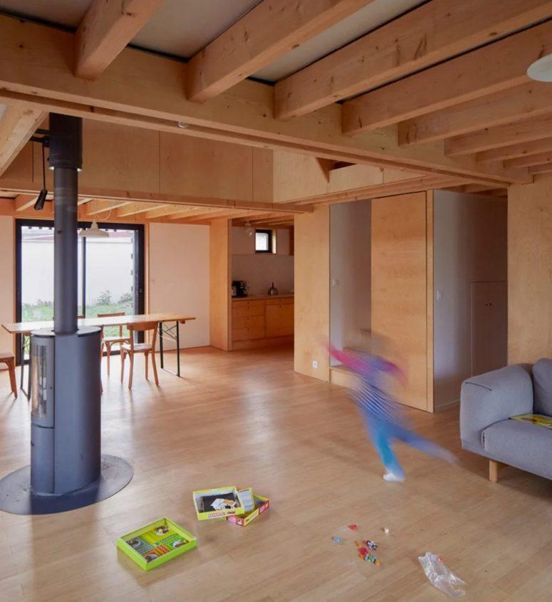 La disposition principale comprend une cuisine, une salle à manger et un salon, elle est entièrement revêtue de contreplaqué de couleur claire et dispose d'un foyer au centre