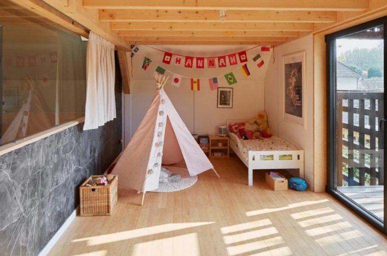 La chambre des enfants comprend un lit, un tipi, des œuvres d'art et des guirlandes audacieuses et une entrée sur le balcon