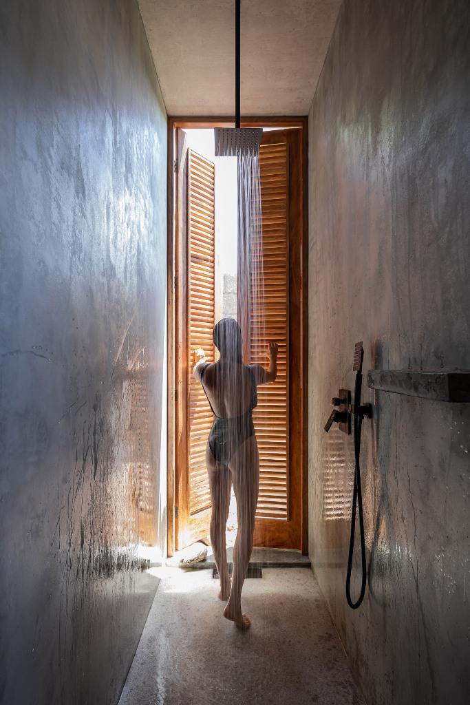 La douche élancée s'ouvre sur l'extérieur avec des portes à volets en bois