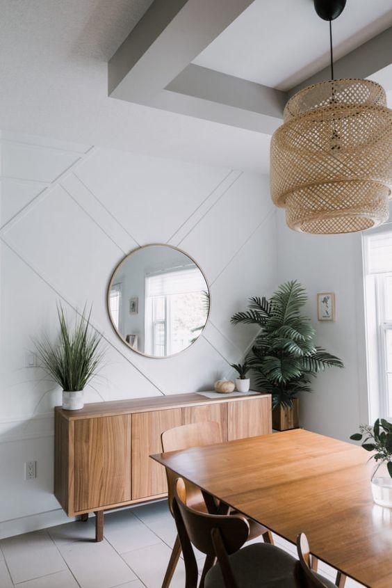 une salle à manger chic et moderne du milieu du siècle avec un mur lambrissé blanc, un élégant mobilier en bois, une suspension en osier et de la verdure