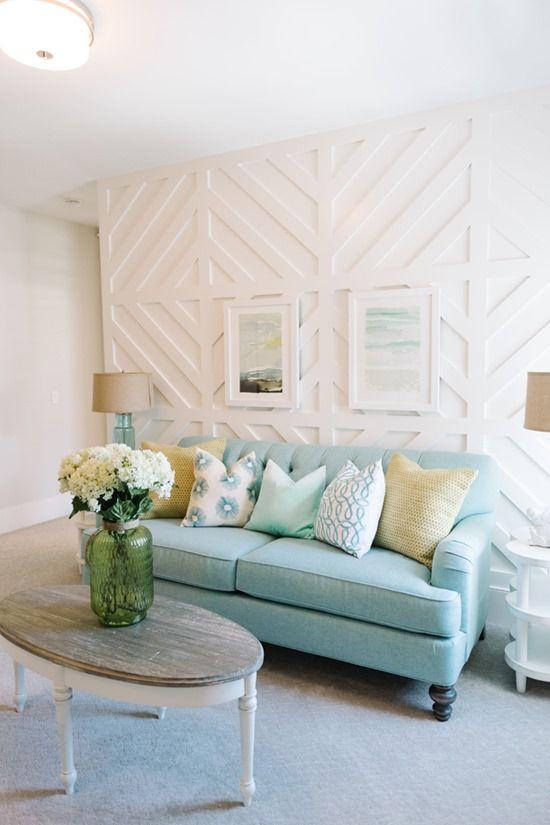un beau salon côtier avec un mur à motif géométrique blanc, un canapé bleu, des meubles blancs, des œuvres d'art et des fleurs blanches