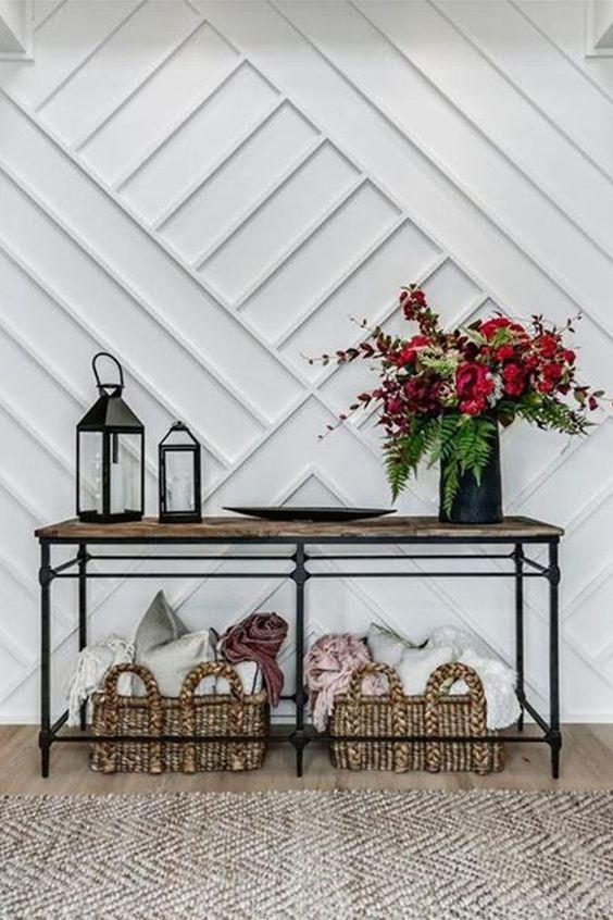 une entrée chic avec un mur lambrissé blanc, une console industrielle, des paniers avec des oreillers et un arrangement floral audacieux