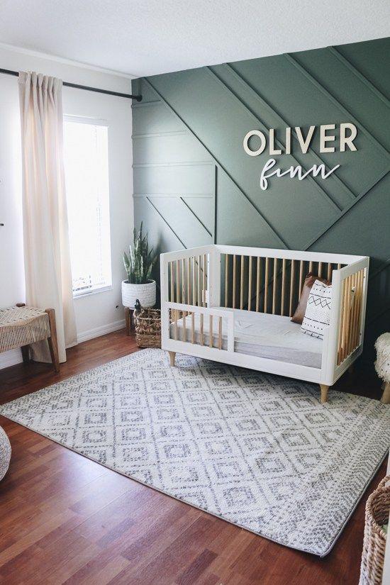 une chambre d'enfant contemporaine chic avec un mur lambrissé vert, des meubles modernes du milieu du siècle, des textiles neutres et de la verdure en pot