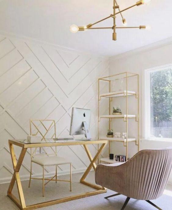 un bureau à la maison glamour avec un mur géométrique lambrissé blanc, une étagère dorée, un bureau et une chaise, une chaise blush et un lustre audacieux