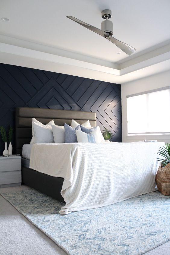 une chambre confortable et aérée avec un mur lambrissé géométrique bleu marine, un lit rembourré en cuir, des tables de nuit neutres, de la verdure dans des vases et des pots