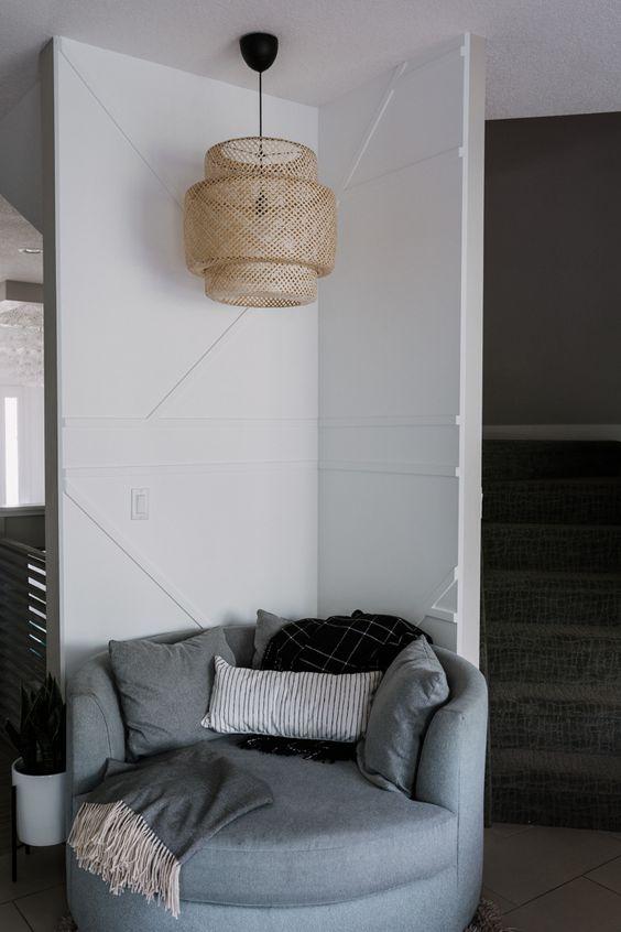 un coin lecture douillet avec un mur géométrique blanc, une suspension en osier et une chaise ronde grise est très accueillant